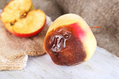 Rotten apples on wooden board on sackcloth — Photo