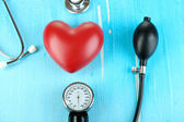 Tonometer, stethoscope and heart on wooden table close-up — Stock Photo
