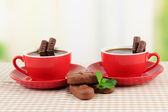Red cups of strong coffee and chocolate bars on tablecloth on bright background — Stock Photo