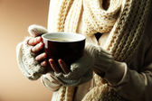 Female hands with hot drink, on color background — Stock Photo