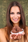 Portrait of beautiful young girl with chocolate candy on shiny background — Stock Photo
