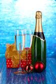 Bouteille de champagne avec des lunettes et des boules de noël sur la table en bois sur fond bleu — Photo
