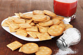 Delicious crackers with salt and tomato juice on wooden background — ストック写真