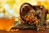 Zweige der sanddorn mit tee und holz korb auf tisch mit hellem hintergrund — Stockfoto