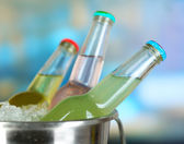 Bottled drinks in ice bucket on bright background — Photo