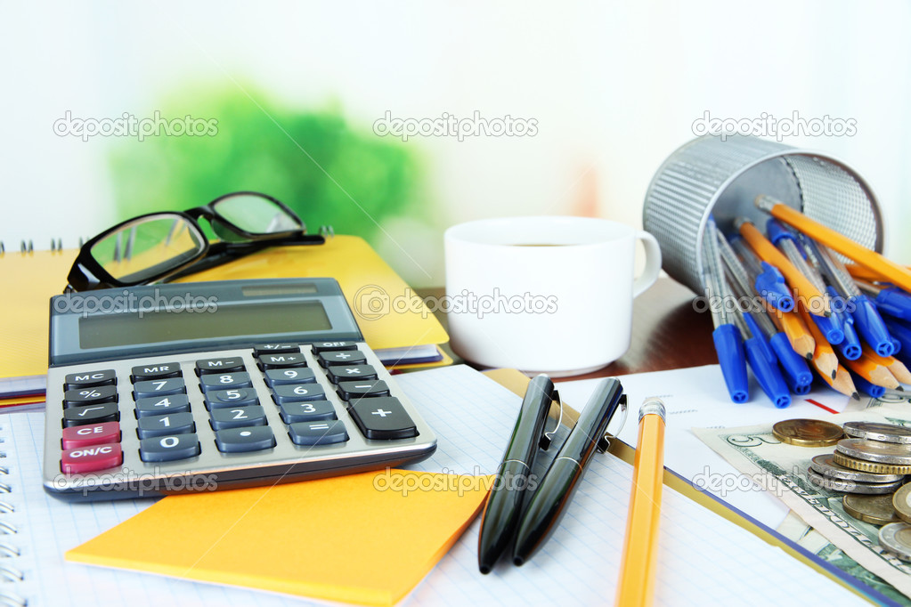 Office supplies with documents and cup of coffee on table on ...