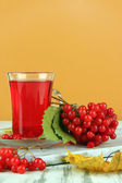Red berries of viburnum and cup of tea on table on beige background — Stock Photo