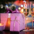 Many gifts and glass of champagne on bright background — Stock Photo