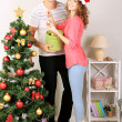 Happy young couple near Christmas tree at home — Photo
