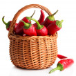 Red hot chili peppers in wicker basket,on sackcloth, isolated on white — Stock Photo