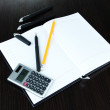 Stock Photo: Notebook with pens,pencil and calculator on wooden background