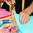 Stock Photo: Cutting fabric with tailors scissors