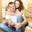 Young couple with boxes in new home on room background — Stock Photo #33736171