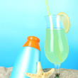 Beach cocktail and sunscreen in sand on blue background — Stock Photo
