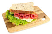 Tasty sandwich with salami sausage and vegetables on cutting board, isolated on white — Stock Photo