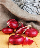 Fresh red onions on wooden table — Stock Photo