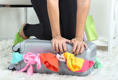 Suitcase with clothes on carpet on room background — 图库照片