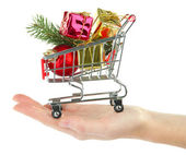Hand holding Christmas gifts in shopping trolley, isolated on white — ストック写真