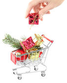 Hand and Christmas gifts in shopping trolley, isolated on white — Stock Photo