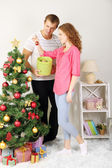 Happy young couple near Christmas tree at home — 图库照片
