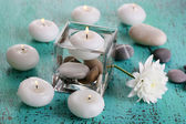 Decorative vase with candles, water and stones on wooden table close-up — Stock Photo