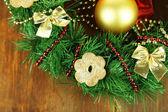 De kroon van kerstmis versierd met cookies op houten achtergrond — Stockfoto