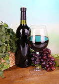 Ripe green and purple grapes in basket with wine on wooden table on bright background — Stock Photo