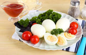 Boiled eggs on plate on napkin on wooden table — Stock Photo