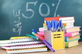 Kancelářské potřeby na tabulce na školní rada pozadí — Stock fotografie