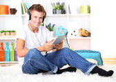 Young man relaxing carpet and listening to music — Стоковое фото