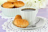 Tasty croissants and cup of coffee on table close-up — Stock Photo