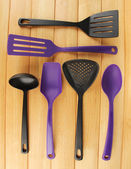 Plastic kitchen utensils on wooden background — Zdjęcie stockowe