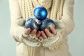 Female hands in mittens Christmas tree balls, on color background — Stock Photo