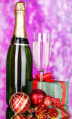 Bottle of champagne with glass and Christmas balls on purple background — Stok fotoğraf