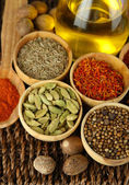 Many different spices and fragrant herbs on braided table close-up — Foto de Stock