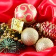 Beautiful Christmas decor on red satin cloth — Stock Photo #33931327