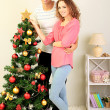 Happy young couple near Christmas tree at home — Lizenzfreies Foto