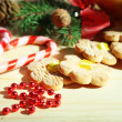 Cookies on ribbons with Christmas decorations on wooden table — Stock Photo