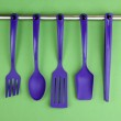 Plastic kitchen utensils on silver hooks on green background — Stock Photo #33932169