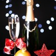 Bottle of champagne with glass and Christmas balls on Christmas lights background — Stock Photo