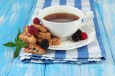 Tasse tee mit keksen und beeren mit tabelle nahaufnahme — Stockfoto