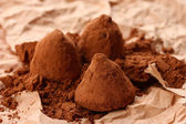 Chocolate truffles and cocoa, on brown background — Stock Photo