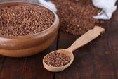 Buckwheat groats in bowl and wooden spoon closeup — Stock Photo