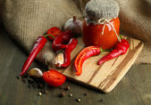 Composition with salsa sauce in glass jar,, red hot chili peppers and garlic, on sackcloth, on wooden background — Stock Photo