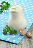 Sour cream in pitcher on table close-up — Stock fotografie