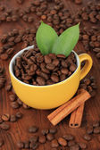 Coffee beans in cup on wooden background — Stock Photo