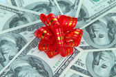 Dollars with gift bow close-up — Stock Photo