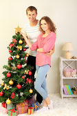 Happy young couple near Christmas tree at home — Stok fotoğraf