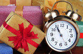 Alarm clock with Christmas tree and presents on wooden table close up — Foto Stock
