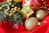 Beautiful Christmas decor on red satin cloth — Stock Photo